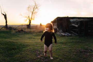 Toddler girl dancing outside at sunset.
