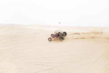A sand rail speeding along the ridge of a sand dune