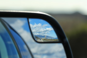 Road, sky and clouds in rear view mirror
