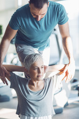 Woman Doing Exercise  with her Fitness Instructor in the Gym