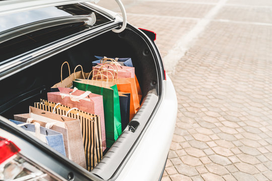 Shopping bags in car trunk or hatchback, with copy space. Modern shopping lifestyle, rich people or leisure activity concept