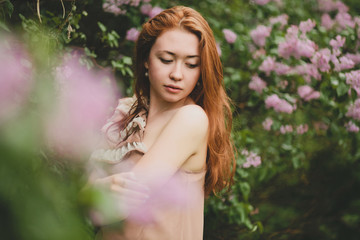 Portrait of beautiful young woman in blossom garden