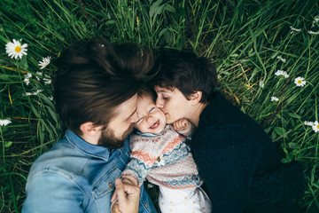 Young couple laying in chamomile field playing with baby girl