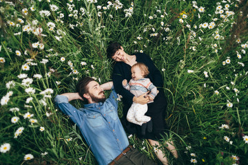 Young couple and their baby girl laying in camomile field
