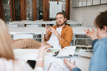 Portrait of young man with blond hair and beard sitting throw his legs on table and using cellphone in classroom. Group of students studying together. Boy thoughtfully looking at his classmates