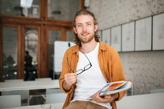 Young man sitting on table in office with glasses and document case in hands. Portrait of smiling boy with blond hair and beard joyfully looking in camera while holding documents in hand