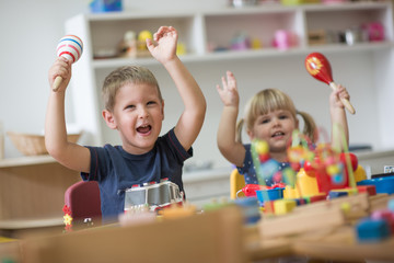 Happy smiling caucasian kids are playing with montessori toys