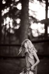Little Girl In Forest Holding Edges Of Dress