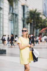 Blonde Woman Carrying Shopping Bags on the Street