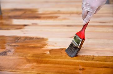 Hand varnishing wooden floor