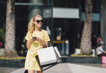Blonde Woman Carrying Shopping Bags and Texting on the Street