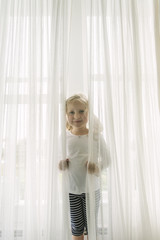 Portrait of Young Girl Hiding in the Curtains