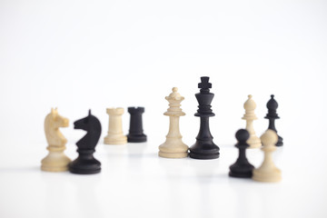 White queen and black king, traditionally confronted in chess game, are together. Image in isolated white background