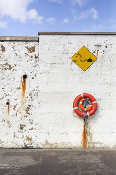 Life boy and sign on harbour wall...