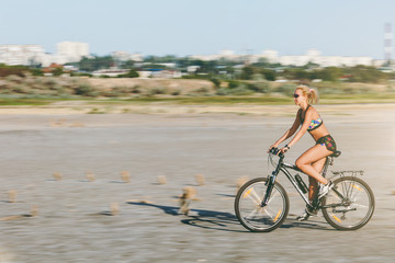 A sporty blonde woman in a colorful suit rides a bike at fast speed in a desert area on a sunny summer day. Fitness concept. Blur background