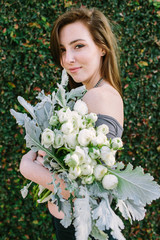A woman holding a beautiful bouquet of white ranunculus.