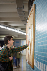 Young student reading good news on a board of the university