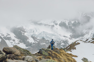 Young alpine climber with blue dress looking from the viewpoint glacier in the Italian Alps