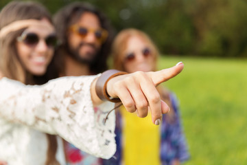 happy hippie woman pointing finger outdoors