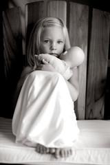 Little Girl In White Slip Dress Holding Baby Doll