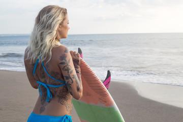 Pensive surf girl looking at the ocean