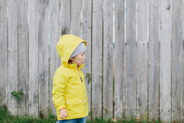 Cute kid in yellow raincoat against of wooden fence