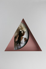 Studio shot of an African American woman behind geometrical shapes