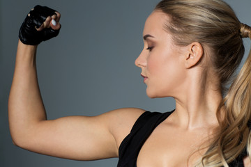 close up of woman posing and showing biceps in gym