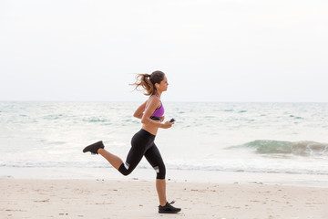Woman running on the beach - fitness outdoors