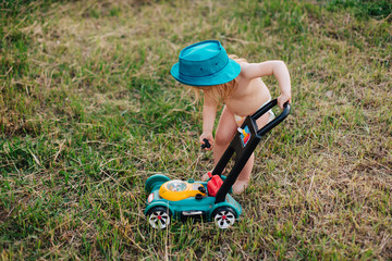 Toddler girl in diaper playing outside with pretend lawnmower.