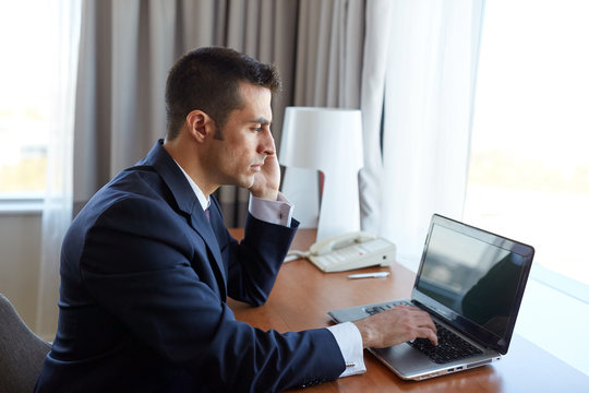 businessman with laptop and smartphone at hotel