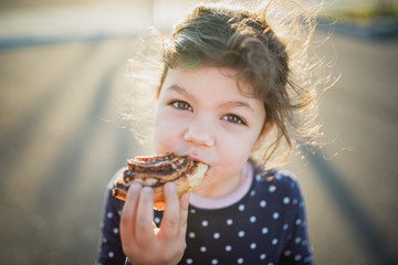 Portrait of a girl eating chocolate rolls