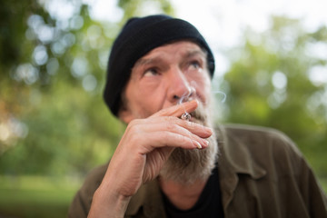 Close up view of old man smoking. male in the street with cigarette. image with selective focus.