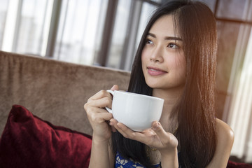 Beautiful Asian girl with cup of cofee mocha drinking in luxury home with sunlight in windows.  Copy space for text.