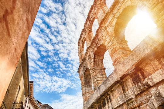 Arena of Verona, ancient roman amphitheater in Italy during sunrise and blue sky with clouds.