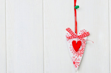 Red and white handmade heart on white wooden background. Copy space.