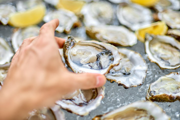 Open oyster in a male hand, against the background of open oyste