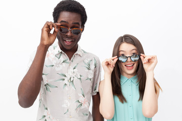 Smiling mixed couple in sunglasses