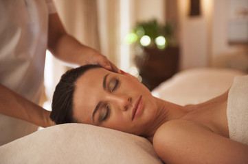 Woman receiving face massage at spa