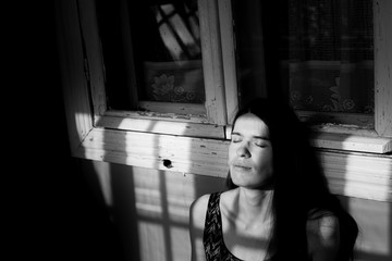 Young woman basking in the rays of the sun in the shadow of the window frames on the porch. Black-and-white photography.