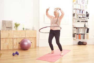 Senior woman using hula hoop