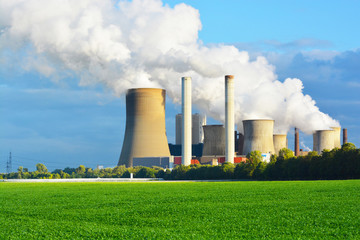 Environmental destruction with polluting power plant at horizon, against green meadow
