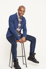 Young man in denim jacket sitting on stool