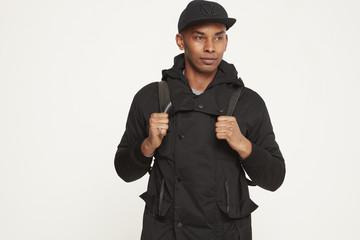 Young man wearing baseball cap and black coat