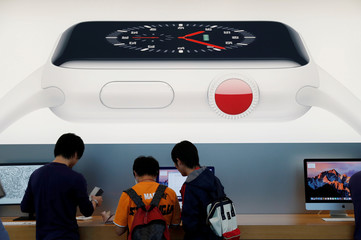 Customers are seen under a picture of new Apple Watch Series 3 after it goes on sale at the Apple Store in Tokyo's Omotesando shopping district
