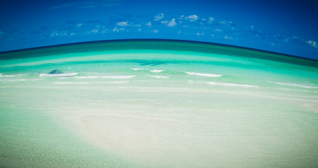 abstract amazing view of tropical beach with rising curved ocean horizon line and dark blue sky background on sunny beautiful day