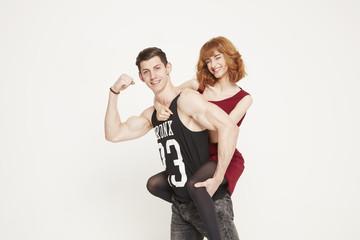 Muscular young man giving young woman piggyback ride