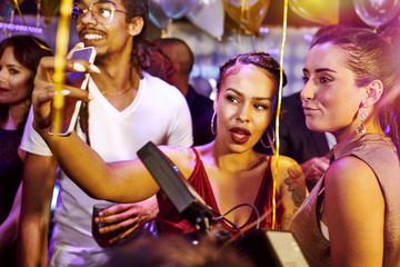 Friends taking selfie at nightclub