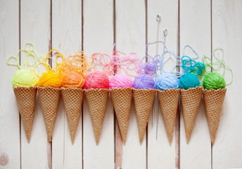 Balls of yarn lie in a waffle cone for ice cream. Coloured wool.