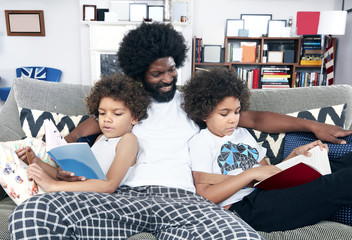 Children reading books on sofa with father
